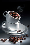 Coffee Beans With Cup. Still shot on white cup with coffee beans in mood lighting Royalty Free Stock Image