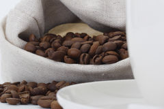 Coffee beans and cup. Coffee beans spilled out of the bag Stock Images