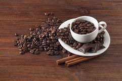 Coffee beans in a cup. Coffee beans in the cup on the table with two cinnamon sticks Stock Photo