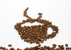 Coffee beans cup. Shape made with fresh roasted coffee beans and beautiful DOF Royalty Free Stock Image