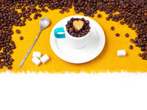 Coffee beans in a cup. Aromatic coffee beans in a cup on a plate with a spoon and sugar on an orange tablecloth Royalty Free Stock Photos