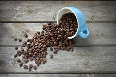 Coffee Beans Cup Background. A blue coffee cup full of coffee beans spilling out on a wood background Royalty Free Stock Photo