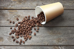 Coffee Beans Cup Background. A paper coffee cup full of coffee beans spilling out on a wood background Royalty Free Stock Images