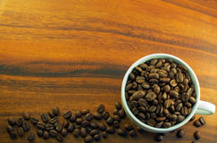 Coffee beans in a cup background. Whole coffee beans in a cup on a wooden background Stock Photos