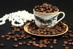 Coffee beans in a cup and beads. Coffee beans in a cup of oriental style and beads Royalty Free Stock Photo