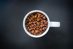 Coffee beans in a cup. On black background royalty free stock images