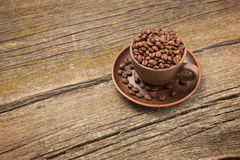 Coffee beans in a cup on the boards royalty free stock photos