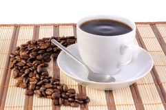 Coffee beans and cup with coffee. White cup with coffee on bamboo mat and coffee beans Stock Photography