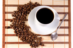 Coffee beans and cup of coffee. White cup with coffee on bamboo mat and coffee beans stock images