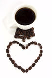Coffee beans and cup of coffee. Heart made of coffee beans and cup of coffee isolated at the white background Stock Photo