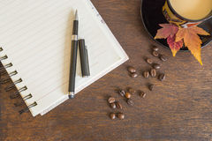 Coffee beans, cup of coffee, autumn leaves, notebook on wooden deck Stock Photos