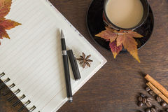 Coffee beans, cup of coffee, autumn leaves, pen and notebook on wooden deck Stock Image