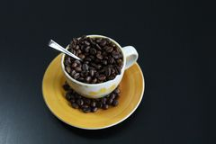 Cup of coffee with beans. Coffee beans in a cup of coffee, black background, copyspace royalty free stock photos