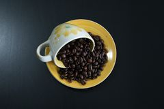Cup of coffee with beans. Coffee beans in a cup of coffee, black background, copyspace royalty free stock photography