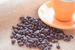 Coffee beans and Cup of coffee on brown fabric paper Royalty Free Stock Photos