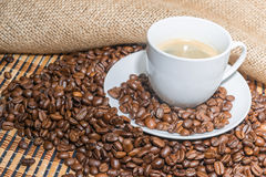 Coffee beans and cup of coffee. Coffee beans and cup of coffee on burlap Stock Photos