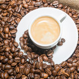 Coffee beans and cup  of coffee. On burlap background Stock Image