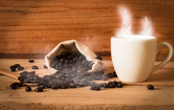 The coffee beans and cup of coffee with smoke on wooden table ba Stock Photos