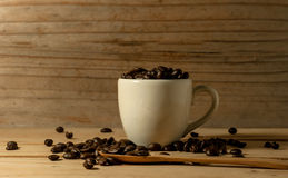 The coffee beans and cup of coffee with spoon onwooden table bac. Coffee beans and cup of coffee with spoon onwooden table background. still life process Royalty Free Stock Image