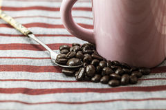 Coffee beans and a cup of coffee. On a tablecloth Stock Photos