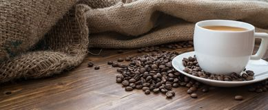 Coffee beans, caffee. Coffee beans with cup of coffee on wooden table, brown, warm, shallow, detail Royalty Free Stock Photos