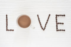 Coffee beans with cup of coffee on wooden table. Love coffee concept Stock Photos