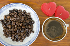 Coffee beans an cup of coffee on a wooden table Royalty Free Stock Photo