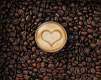 Coffee beans with cup and cream with heart. In coffee beans Royalty Free Stock Photos