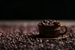 Coffee beans in a cup. A cup full of coffee beans, black background Royalty Free Stock Photo