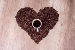 Coffee beans and cup on heart. On wooden Stock Photos