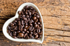 Coffee beans in a cup heart on wooden Royalty Free Stock Photos