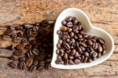 Coffee beans in a cup heart on wooden Royalty Free Stock Photography