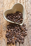 Coffee beans in a cup heart on wooden Stock Image