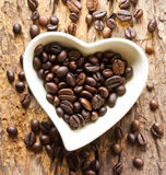 Coffee beans in a cup heart on wooden Royalty Free Stock Photo