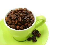 Coffee beans cup isolated on white (clipping path included). Green cup full of coffee beans (clipping path included Royalty Free Stock Photos