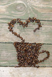 Coffee beans. Coffee cup made from beans, grain with heart on wooden background. Valentine's Day Royalty Free Stock Image