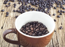 Coffee beans in cup on the old table wooden Stock Image