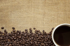Coffee Beans and Cup over Burlap. Border of coffee beans with coffee cup, over burlap background.  Lots of copy space Royalty Free Stock Photography