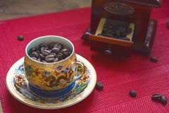 Coffee beans in a cup with a pattern royalty free stock image