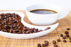 Coffee Beans. Cup of coffee and coffee beans on a placemat in front of the window Royalty Free Stock Photos