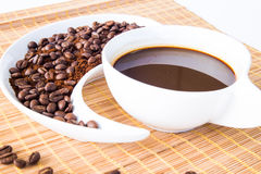 Coffee Beans. Cup of coffee and coffee beans on a placemat in front of the window Royalty Free Stock Images