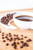 Coffee Beans. Cup of coffee and coffee beans on a placemat in front of the window Stock Images