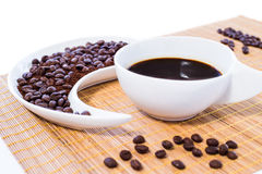 Coffee Beans. Cup of coffee and coffee beans on a placemat in front of the window Royalty Free Stock Photo
