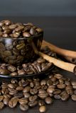 Coffee beans, cup, Pots, cinnamon on dark Stock Image