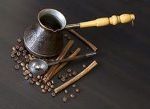 Coffee beans, cup, Pots, cinnamon on dark Royalty Free Stock Image