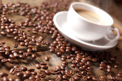 Coffee beans and cup in relaxed atmosphere, warm colors and soft. Focus Stock Photography