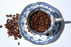Coffee beans in cup and saucer Royalty Free Stock Image