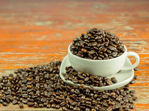 Coffee beans in a cup and spilling out of a cup. Royalty Free Stock Image