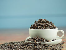 Coffee beans in a cup and spilling out of a cup, on Wooden table . Royalty Free Stock Images
