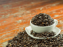 Coffee beans in a cup and spilling out of a cup, on Wooden table . Royalty Free Stock Photography